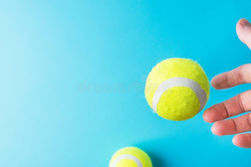 Fangendes Fliegen der Jungefrau Hand, dasin den gelben Tennisbällen der Luft auf hellblauem Hintergrund frei schwebt Aktiver Lebe stockbild
