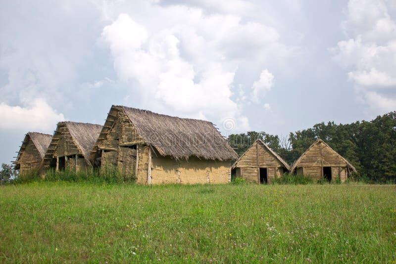Fango neolítico, pueblo de la casa de la suciedad con el tejado cubierto con paja el la primavera m fotos de archivo libres de regalías