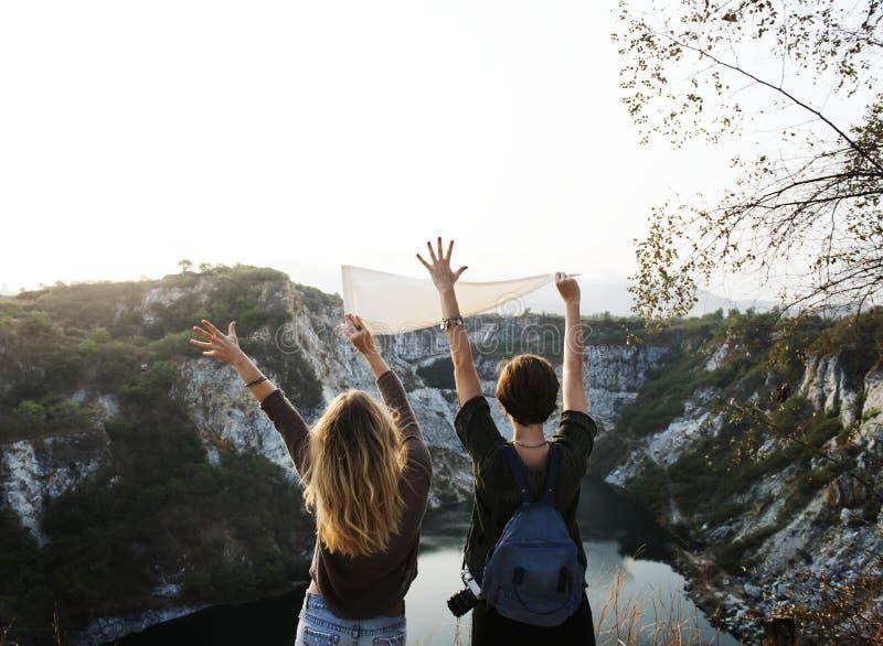 Fanion blanc de participation d'homme près de la fille soulevant deux mains devant le lac entouré par des montagnes image stock