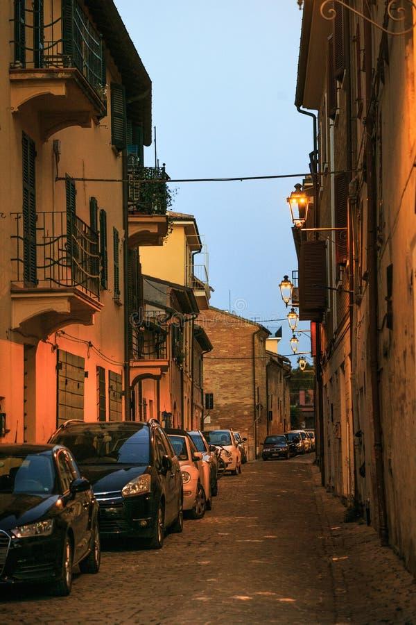 Fano, Italië - Augustus 8, 2017: smalle die straat door straatlantaarns bij nacht in de oude stad wordt aangestoken stock fotografie