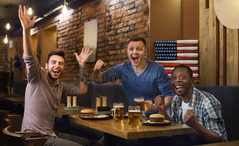 Fans américains observant la partie de football et buvant de la bière photographie stock libre de droits