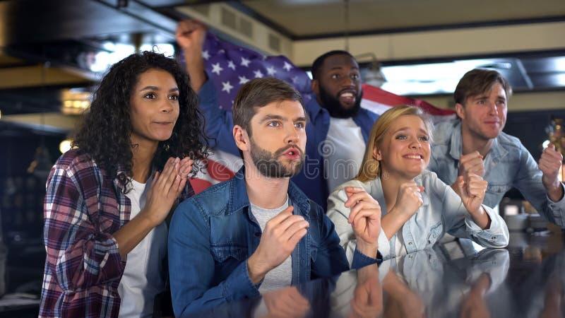 Fans americanos nerviosos que miran la competencia de deporte el apoyar del equipo nacional imagen de archivo libre de regalías