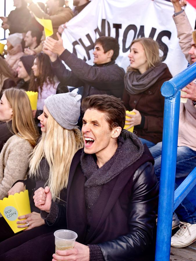 Fans cheering in stadium and eating popcorn. Group young people friends support your favorite team and hands up. Beginning of football match royalty free stock images