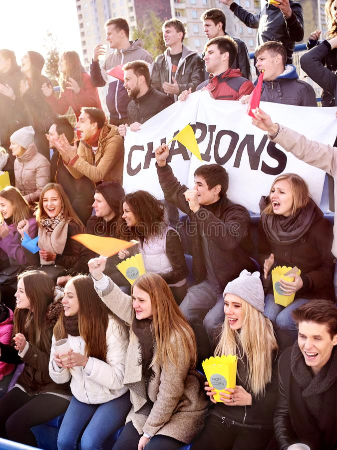 Fans cheering in stadium and eating popcorn. Fans cheering in stadium and eating popcorn in yellow boxes and drink beer. Group young people friends support your royalty free stock photography
