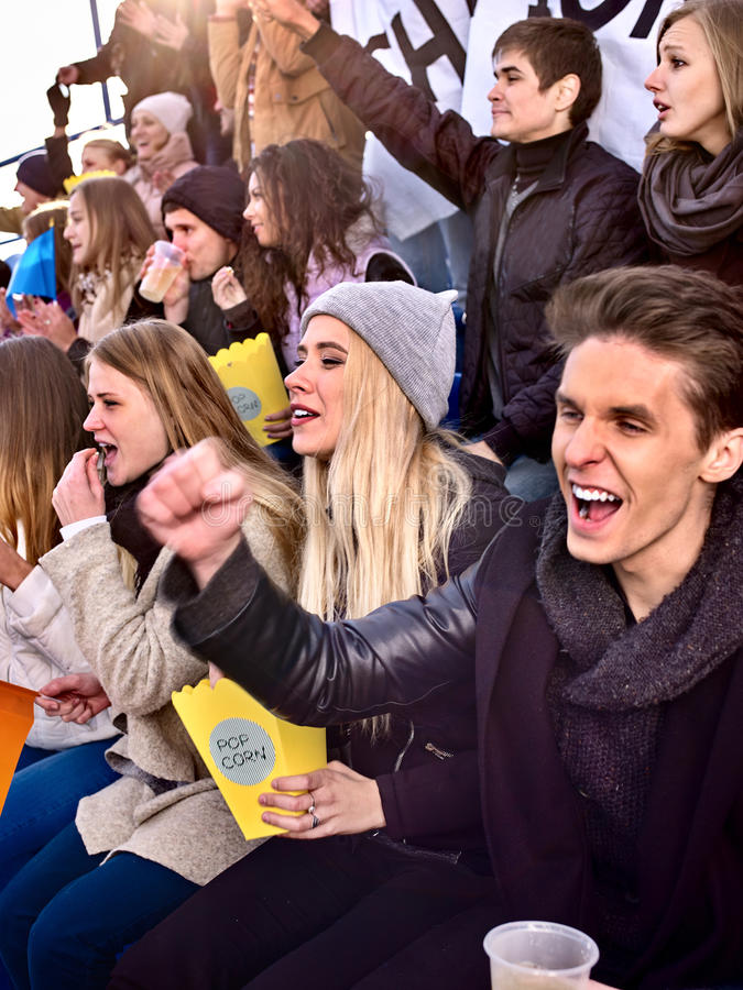 Fans cheering in stadium and eating popcorn. Group young people friends support your favorite team and hands up royalty free stock image