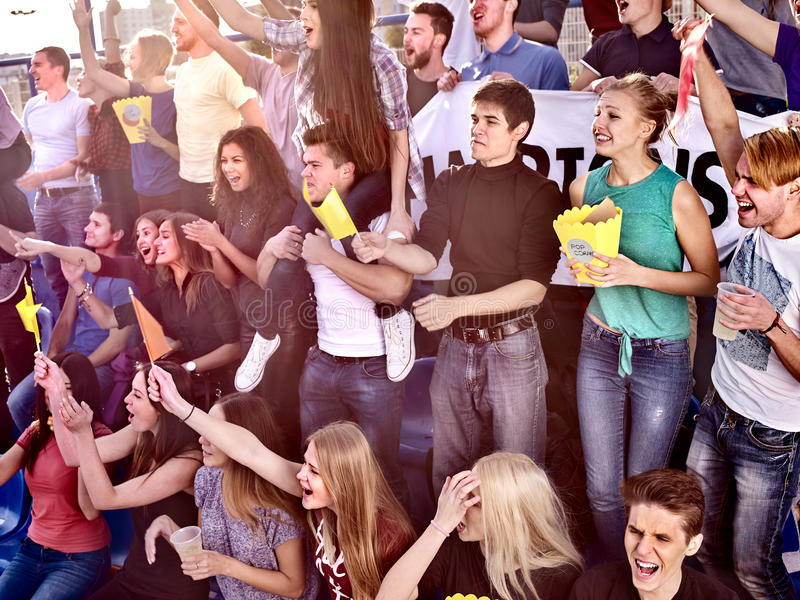 Fans cheering in stadium and eating popcorn. Fans cheering in stadium and eating popcorn in yellow boxes and drink beer. Group young people friends support your royalty free stock photos