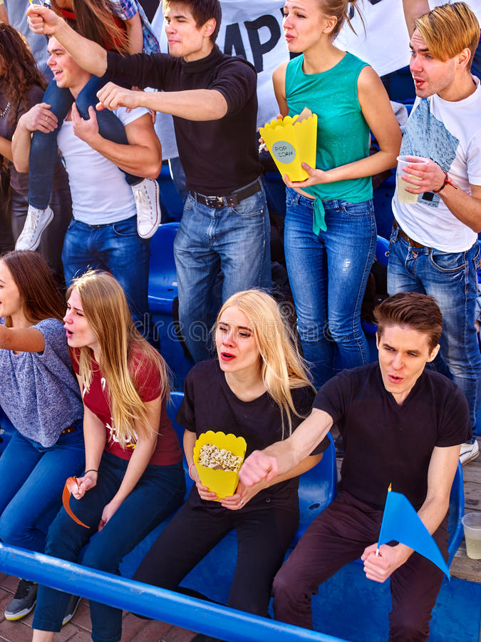 Fans cheering in stadium and eating popcorn. Fans cheering in stadium and eating popcorn in yellow boxes. Group young people friends support your favorite team royalty free stock photos