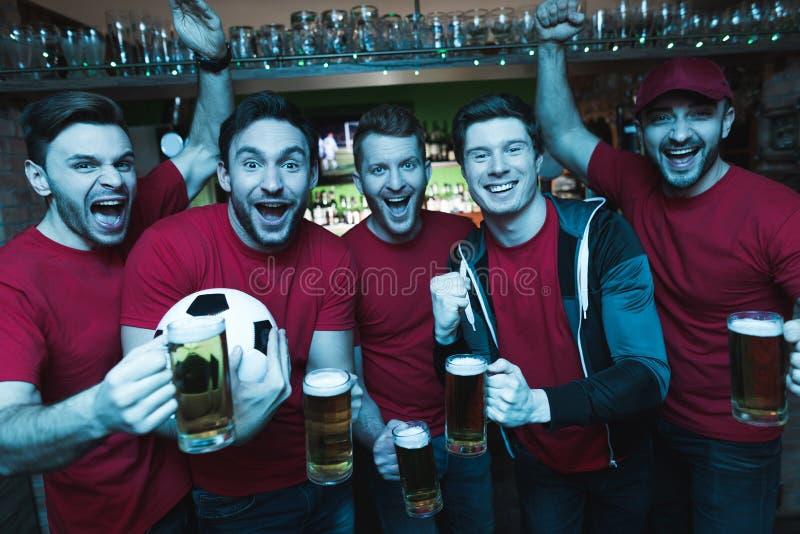 Fans de foot célébrant et encourageant devant la bière potable de TV à la barre de sports photographie stock