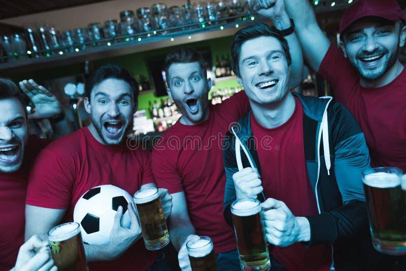 Fans de foot célébrant et encourageant devant la bière potable de TV à la barre de sports photo libre de droits