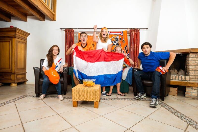 Fans de foot encourageant tout en regardant la rencontre à la maison photographie stock