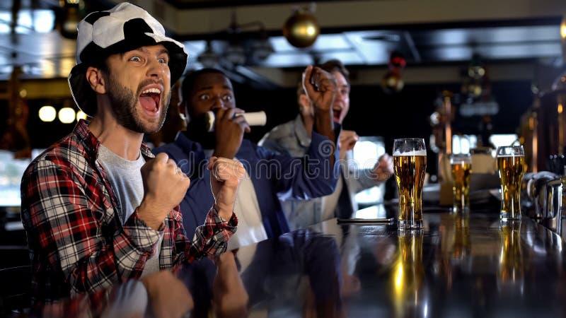 Fans de foot extrêmement heureux observant le jeu dans le bar, célébrant le but de marquage photographie stock