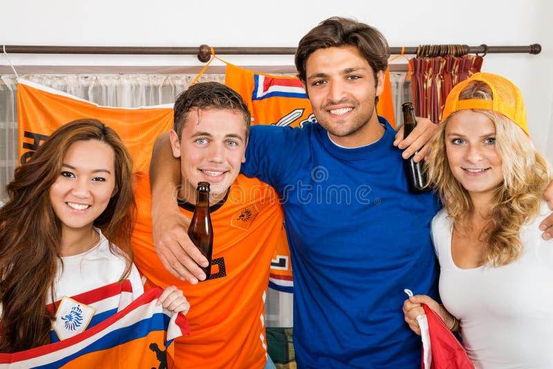 Fans de foot heureux se tenant ensemble à la maison images stock
