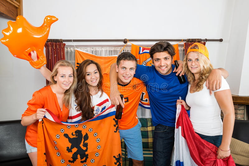 Fans de foot néerlandais heureux se tenant ensemble à la maison photographie stock libre de droits