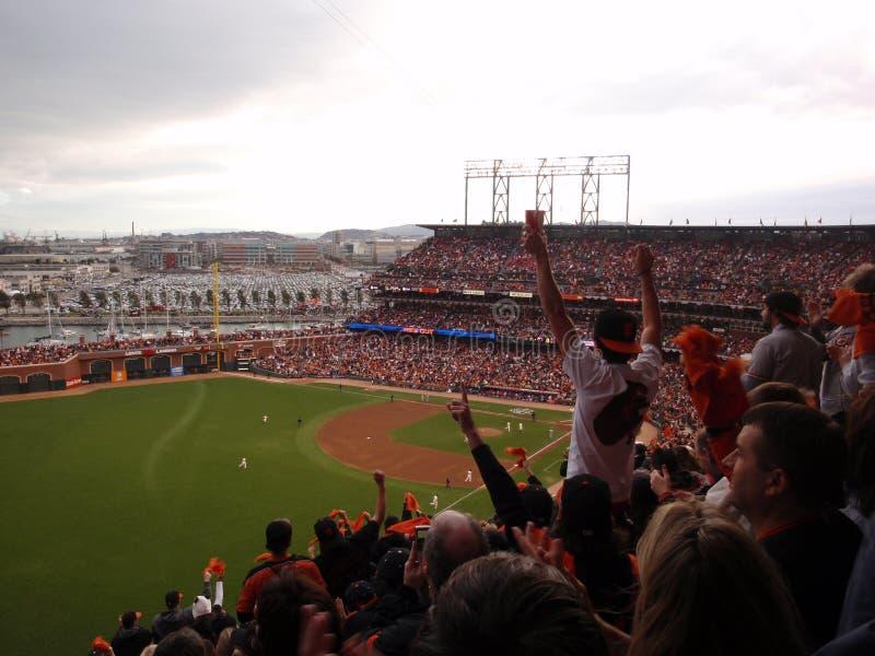 Fans de Giants en la alegría del estadio de béisbol como aumentan las manos adentro foto de archivo libre de regalías