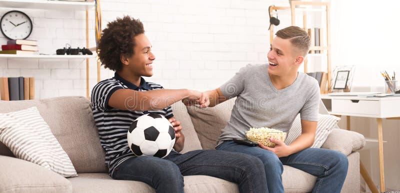 Fans de l'adolescence faisant la bosse de poing tout en observant le football photographie stock libre de droits