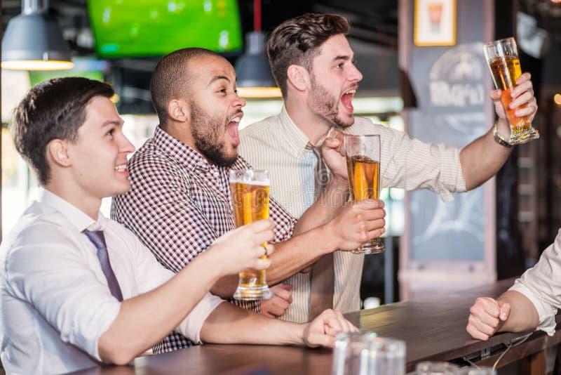 Fans de los hombres que gritan y que miran fútbol en la cerveza de la TV y de la bebida T imagenes de archivo