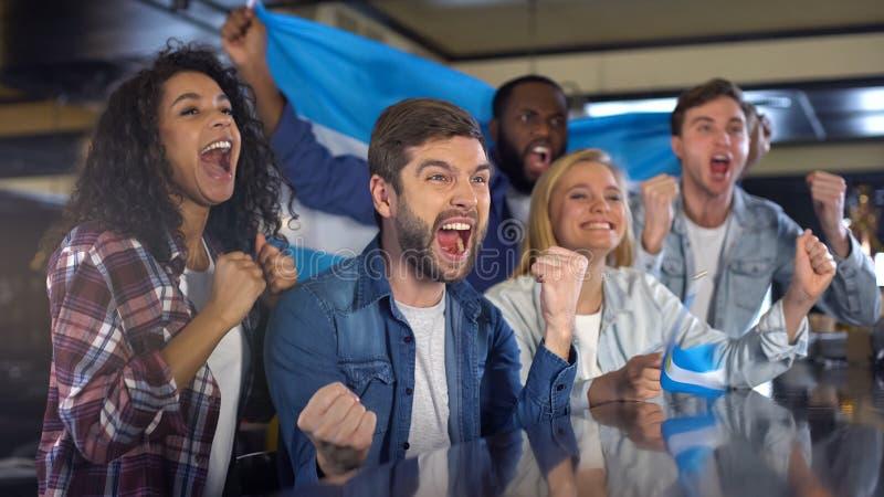 Fans de sports argentins enthousiastes avec le drapeau célébrant la victoire de l'équipe nationale images libres de droits
