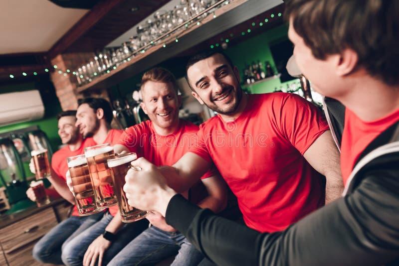 Fans de sports célébrant et encourageant la bière potable à la barre de sports photo libre de droits