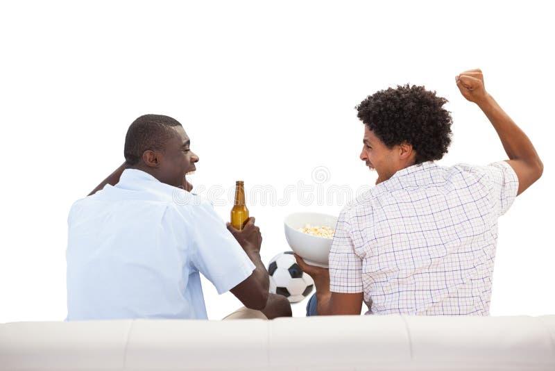 Fans de sports encourageants s'asseyant sur le divan avec des bières photos libres de droits