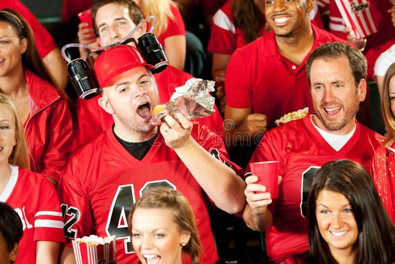 Fans: Den manliga fanen äter på varmkorven med ölhjälmen royaltyfria bilder