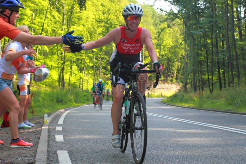 Fans, die Radfahrer auf Rennweg stützen stockfotografie