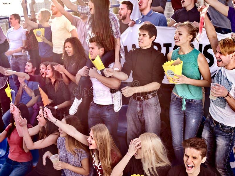 Fans encourageant dans le stade et mangeant du maïs éclaté photos libres de droits