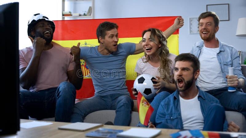 Fans españoles que animan para el equipo de fútbol preferido, celebrando meta que gana fotografía de archivo