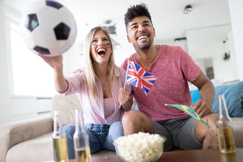 Fans för barnparsport som håller ögonen på matchen på television fotografering för bildbyråer
