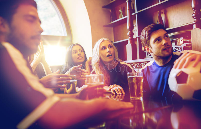 Fans or friends watching football at sport bar stock photography