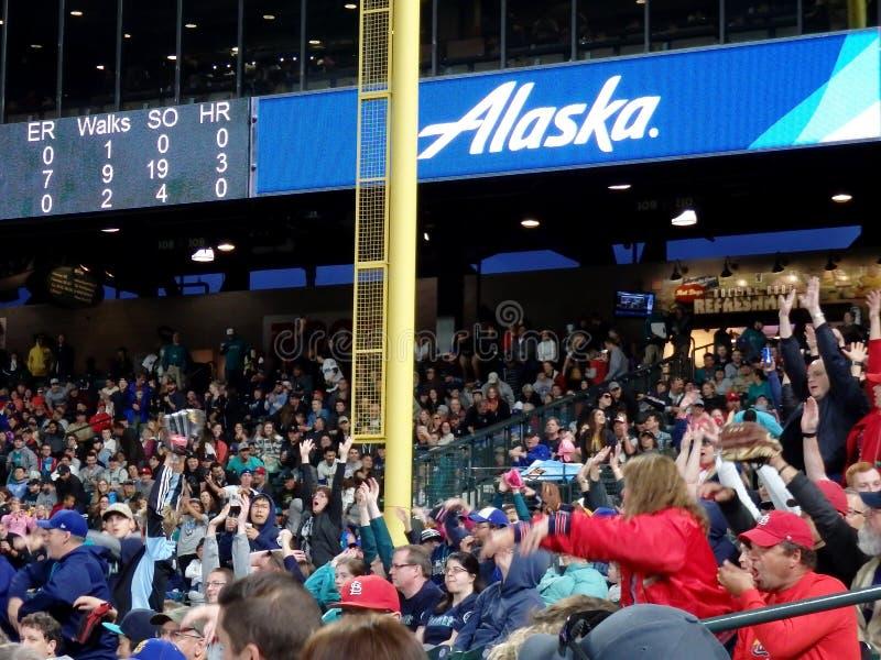 Fans i blekare gör vågen med funktionskortet ovanför att presentera den Alaska Airlines annonsen royaltyfri foto