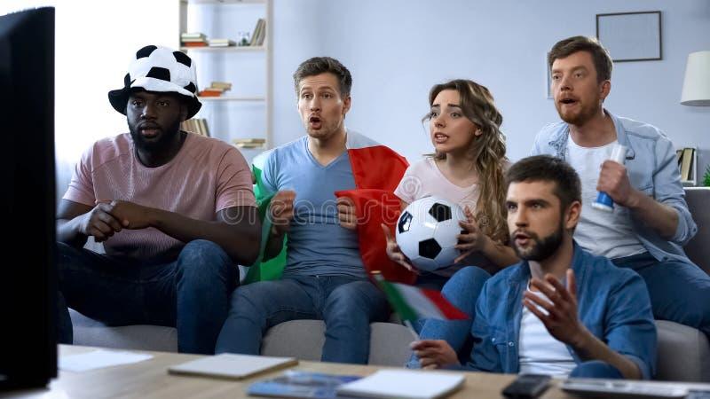 Fans italianas que se sientan en el sofá y el juego de observación, equipo de apoyo, unidad imágenes de archivo libres de regalías