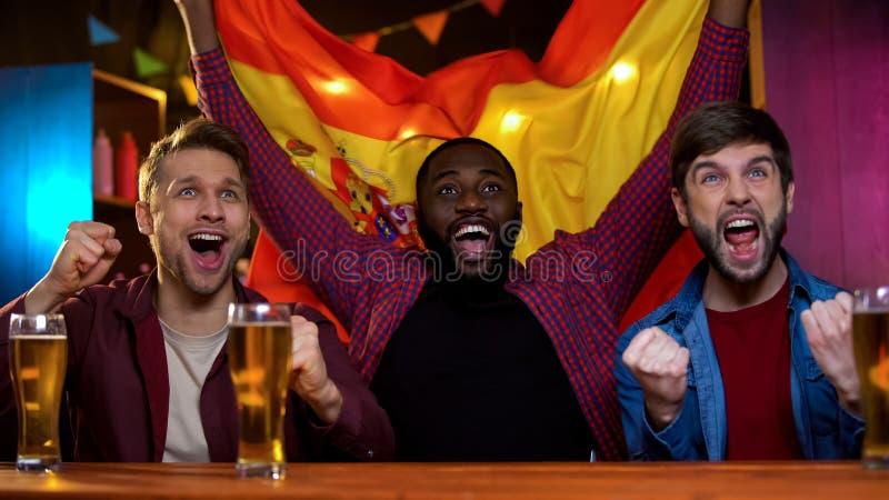 Fans masculinos multirraciales alegres que animan para el equipo de deportes español, bandera que agita imagen de archivo libre de regalías