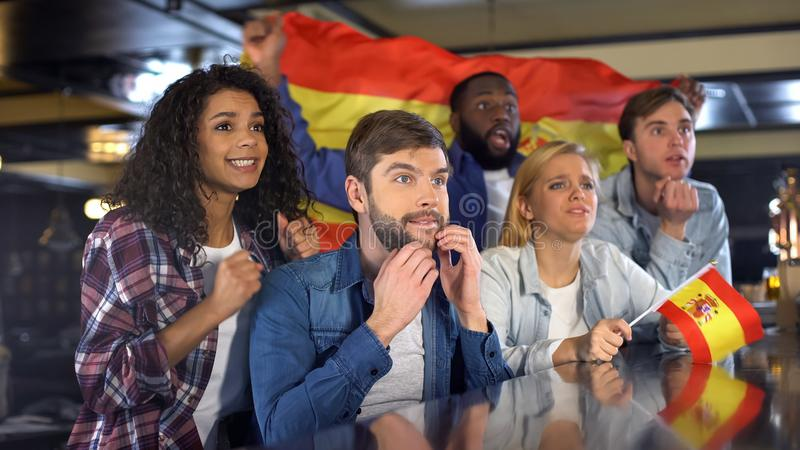 Fans multiétnicos del equipo de deporte español nervioso sobre juego, disfrutando del torneo fotografía de archivo libre de regalías