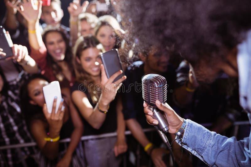 Fans photographiant le chanteur exécutant à la boîte de nuit photos libres de droits