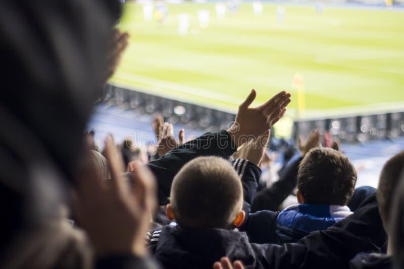 fans que aplauden sus manos en el estadio foto de archivo
