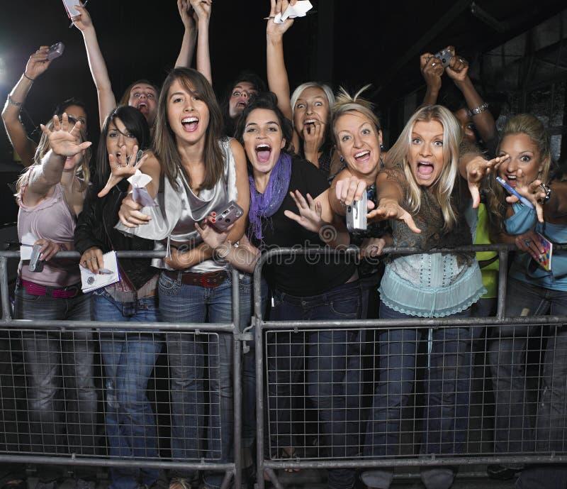 Fans que se inclinan sobre barrera imagen de archivo