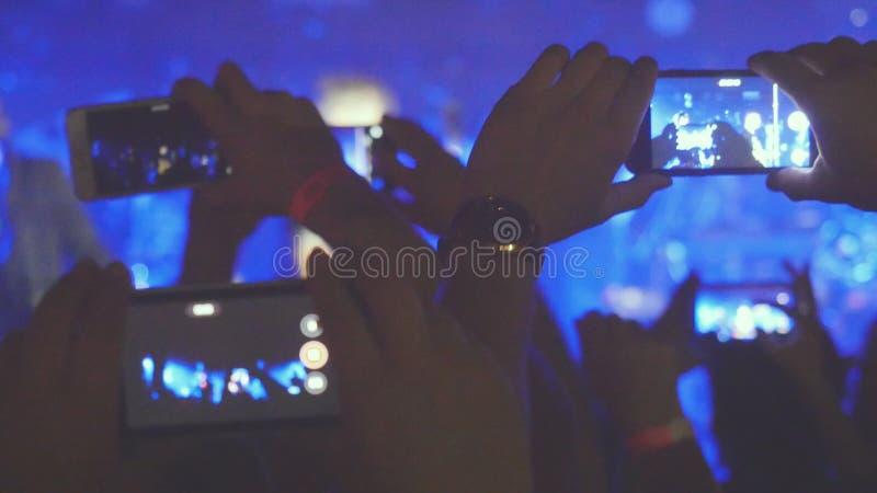 Fans räcker inspelningvideoen och tabilder med smarta telefoner på musikkonserten Folkfolkmassan som festar på, vaggar konsert arkivfoto