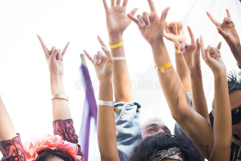 Fans som gör en gest det horn- tecknet med armar, lyftte på musikfestivalen fotografering för bildbyråer