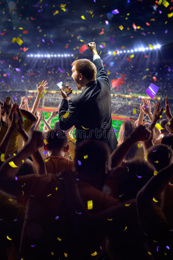 Fans on stadium game businessman. Fans on stadium soccer game Confetti and tinsel stock photo
