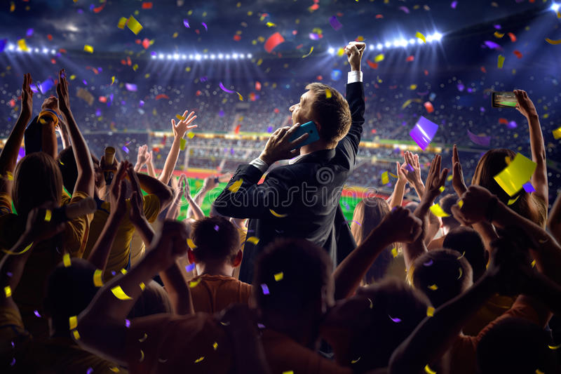 Fans on stadium game businessman. Fans on stadium soccer game Confetti and tinsel stock images