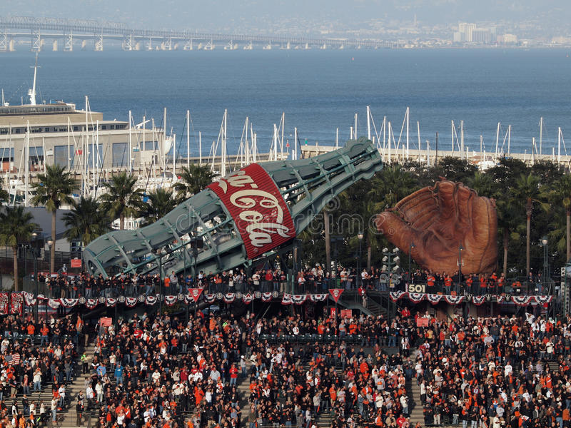 Fans standing with hands on hearts in bleacher section with large glove and giant Coca-Cola slide during National Anthem. SAN FRANCISCO, CA - OCTOBER 20: fans royalty free stock photos