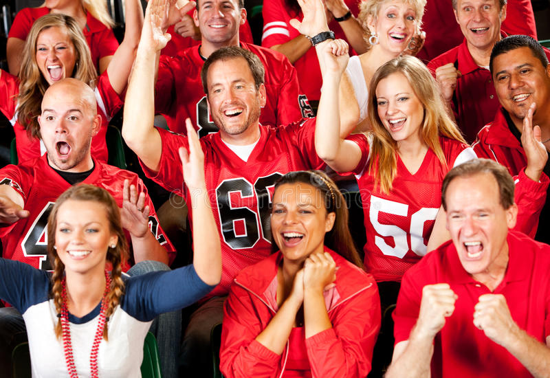 Fans: Team Scores Touchdown and Fans Cheer. Extensive series of a crowd of fans inside a stadium watching their favorite football team. Wearing team jerseys royalty free stock photo