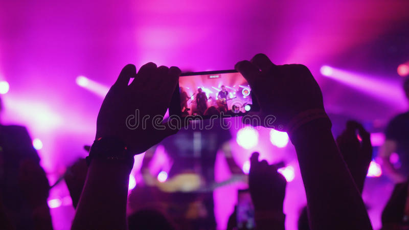 Fans womans hands recording video with smart phones at rock concert on pink colors. Fans hands recording video with smart phones at rock concert on pink colors stock photography