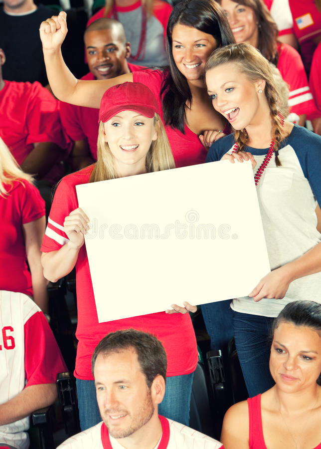 Fans: Women Hold Up Blank Sign. Extensive series of a crowd of baseball fans, sitting in a stadium. Having fun, cheering, etc stock photo