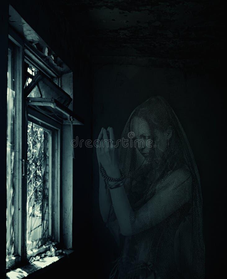 Fantôme de femme de Blured priant dans la vieille maison image stock