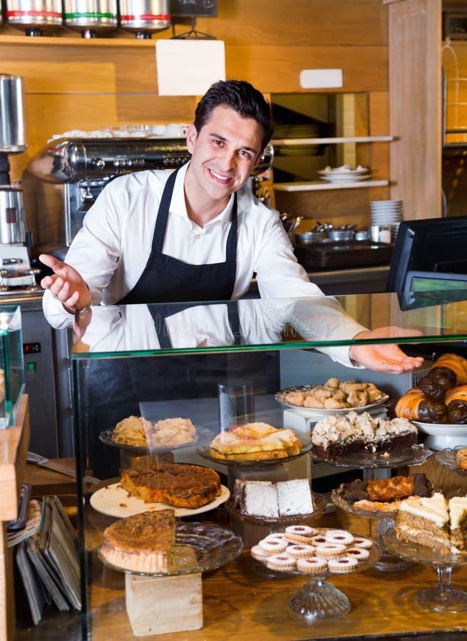 Fantaisie de offre de sourire positive amicale de personnel de café image stock