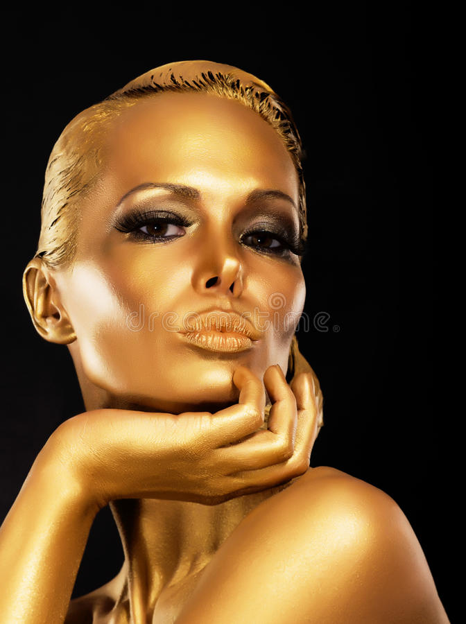 Fantasía. Cara de la mujer enigmática diseñada con maquillaje del oro. Lujo fotografía de archivo