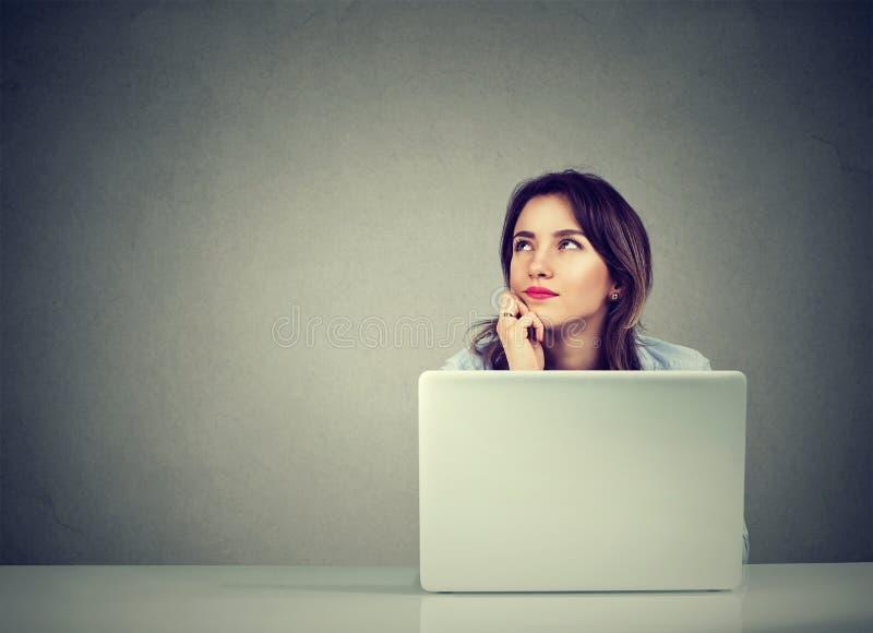 Fantasia de pensamento da mulher de negócio que senta-se na mesa com laptop imagem de stock royalty free