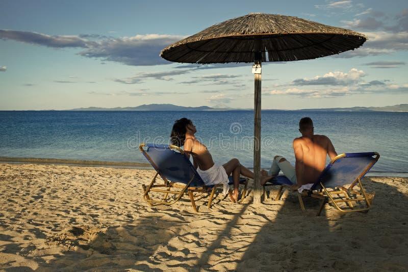 Fantasia di segreti delle coppie La coppia nell'amore alla località di soggiorno del mare si siede sulle chaise-lounge sotto l'om immagini stock libere da diritti
