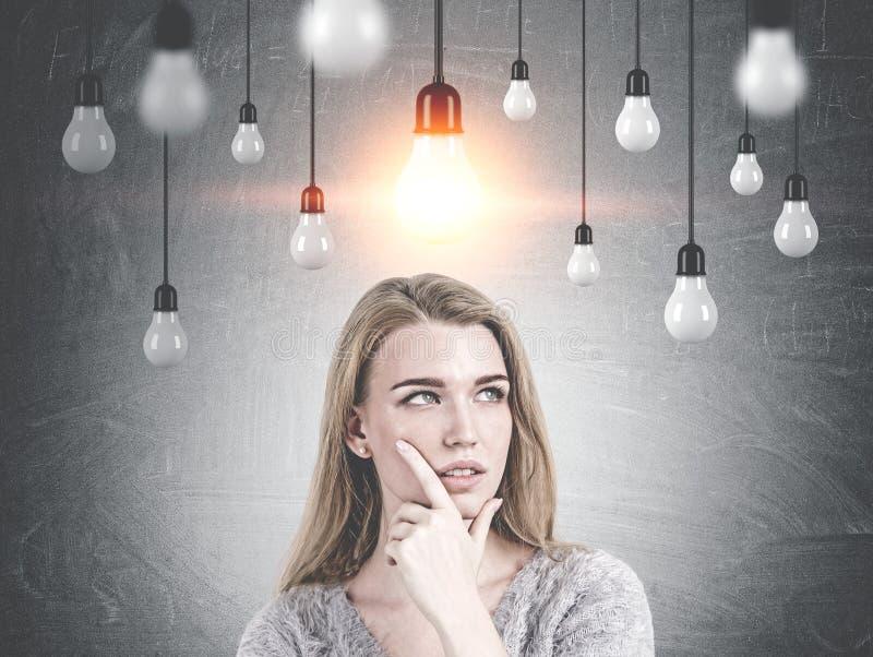 Fantasia loura pensativa da mulher, ideia da ampola imagens de stock royalty free